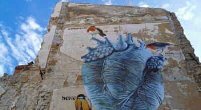 Il cuore che batte sulle macerie: un murale per rinascere